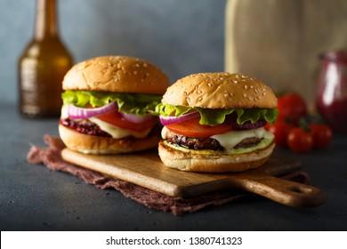 Homemade cheeseburgers on wooden desk