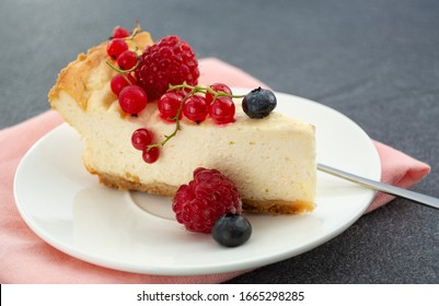 Homemade cheesecake with fresh berries ( raspberry, red currant, blueberry) in the white plate. Close up of the piece of the cake.