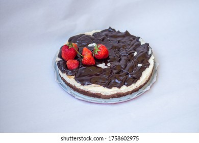 homemade cheesecake with strawberries and chocolate on it with white background