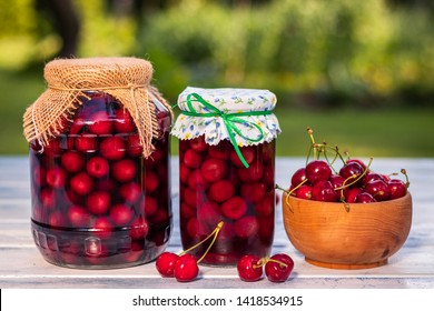 Homemade cherry fruit compote in glass jar and fresh harvested red cherries in wooden bowl. Preserved organic food from garden.