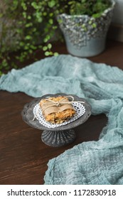 Homemade Chewy Granola Bar on Tin Pedestal with White Heart-Shaped Doily on Wood Table