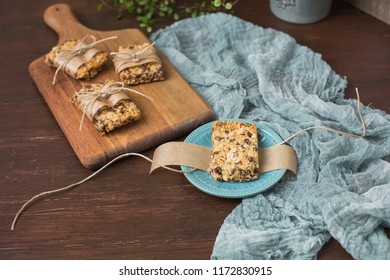 Homemade Chewy Granola Bars Wrapped in Parchment Paper and String on a Wooden Cutting Board; Wood Table Top