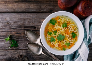 Homemade Chicken and Alphabet Soup with carrots and parsley in bowl on wooden background