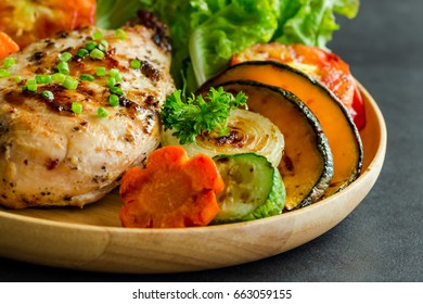 Homemade chicken breast barbecue or steak on wood plate served with grilled vegetables on granite table so soft,moist and delicious for lunch or dinner. Close up view.