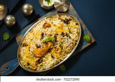 Homemade Chicken Dum Biryani served with raita, Overhead view on dark blue background