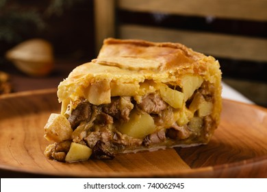 Homemade chicken meat pie with potatoes, apples and chanterelles on rustic wooden background. Piece of pie on a wooden plate