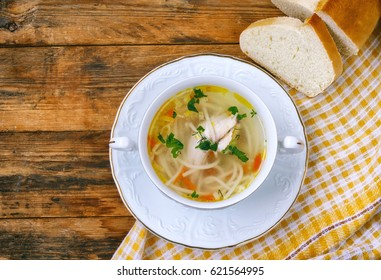 homemade chicken noodle soup,  napkin, bread on a wooden table, rustic style, top view