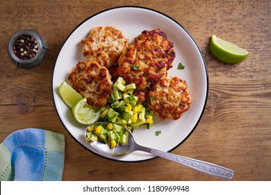 Homemade chicken patties or burgers with avocado corn salsa. overhead, horizontal
