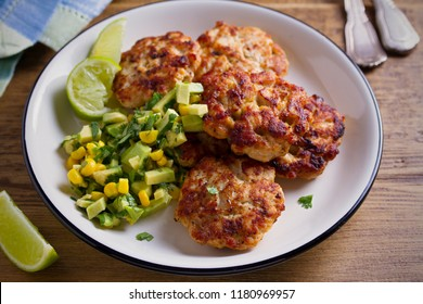 Homemade chicken patties or burgers with avocado corn salsa. horizontal