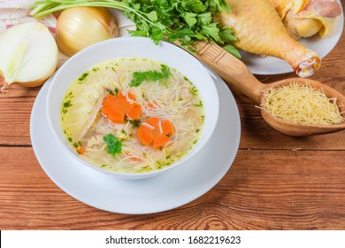 Homemade chicken soup with thin short vermicelli in the white bowl against the some raw ingredients on the rustic table