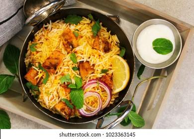 Homemade Chicken Tikka Biryani served with yogurt dip, Overhead view