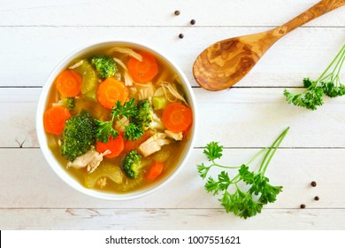 Homemade chicken vegetable soup, above scene on a white wood background