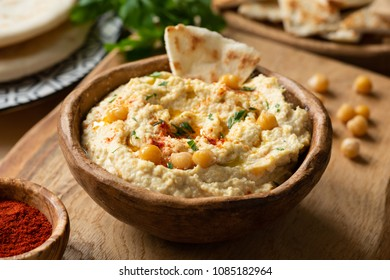 Homemade chickpea hummus bowl with pita chips and paprika. Closeup view, selective focus