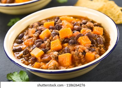 Homemade chili con carne with mincemeat, red and black beans, tomato sauce and pumpkin in enamel bowls, photographed on slate (Selective Focus, Focus one third into the chili)