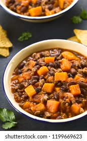 Homemade chili con carne with mincemeat, red and black beans, tomato sauce and pumpkin in enamel bowls, photographed on slate (Selective Focus, Focus one third into the image)