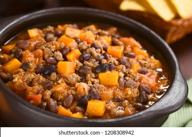 Homemade chili con carne with mincemeat, red and black beans, tomato sauce and pumpkin in rustic bowl with tortilla chips in the back (Selective Focus, Focus in the middle of the dish)