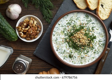 Homemade chilled tarator with ingredients on wooden rustic background. Traditional bulgarian summer cold soup with cucumbers, dill, garlic, yogurt and walnuts.