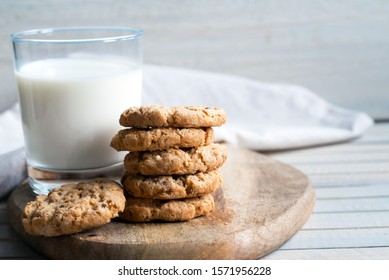 homemade chip cookies and glass of milk on wooden cutting board