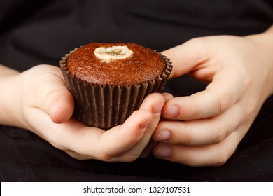 Homemade chocolate banana muffin in children's hands. Dessert for gourmets. Selective focus