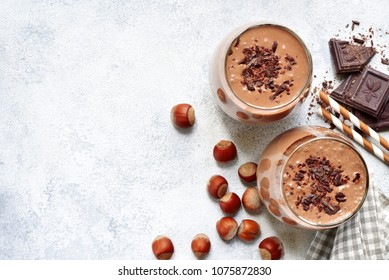 Homemade chocolate banana nut smoothies with ingredients for making over light grey slate, stone or concrete background.Top view with copy space.