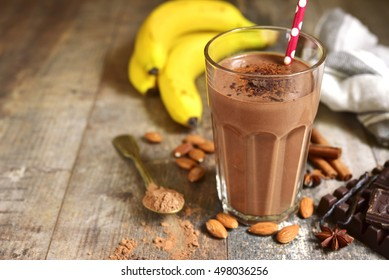 Homemade chocolate banana smoothie in a glass on a rustic wooden background.