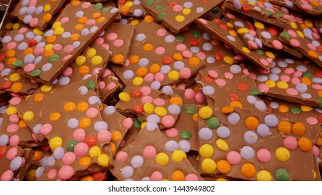 Homemade chocolate bars, decorated with colorful smarties. Background, close-up, format filling.