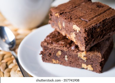 homemade chocolate brownies or chocolate cakes with nuts on white plate, cappuccino, close up