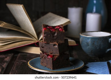 homemade chocolate brownies with cherries on dark background
