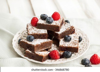 Homemade chocolate brownies decorated with fresh raspberry and blueberry