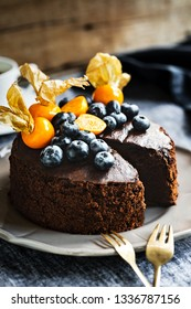 Homemade Chocolate cake with Blueberries and Gooseberry on top by coffee