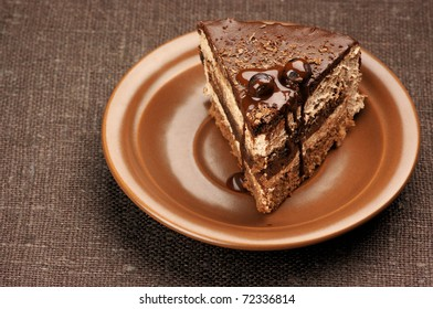 Homemade chocolate cake in brown ceramic plate on brown canvas.