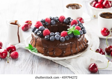 Homemade Chocolate cake with fresh summer berries - raspberry, blueberry, cherry and a cup of coffee on white wooden table, selective focus