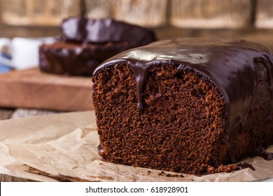 Homemade chocolate cake on baking paper, rustic style