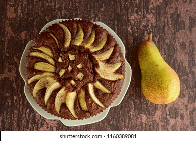 Homemade chocolate cake with pears on wooden background