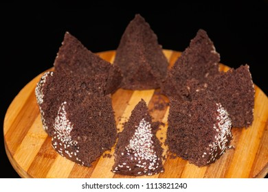 homemade chocolate cake with sesame seeds, sliced on a board