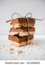 Homemade chocolate caramel slices, bars, millionaires shortbread. Delicious treat. White background. With a string.