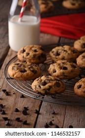 Homemade Chocolate chip cookies on a cooling rack over a wood table with a milk bottle