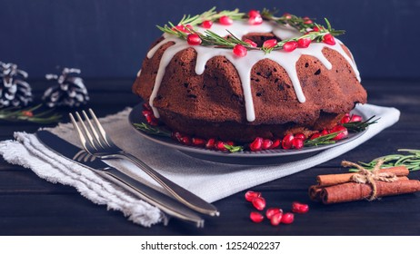 Homemade chocolate Christmas cake decorated with rosemary and pomegranate, front view