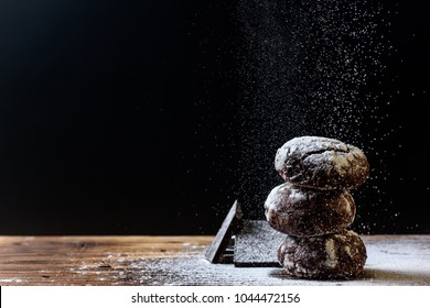 Homemade Chocolate cookies  with chokolate and flour pouder  on a Wood cutting board on a black background. Food horizontal Background. Close up.Photo with text area for design.