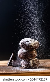 Homemade Chocolate cookies  with chokolate and flour pouder  on a Wood cutting board on a black background.  Food vertical Background. Close up.Photo with text area for design.