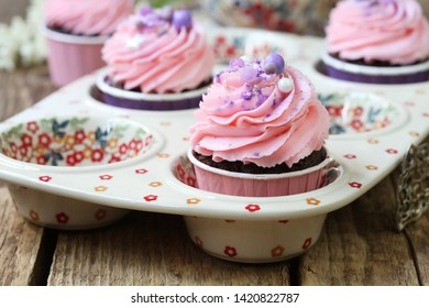 Homemade chocolate cupcakes with pink cream cheese cap on a wooden background. Selective focus