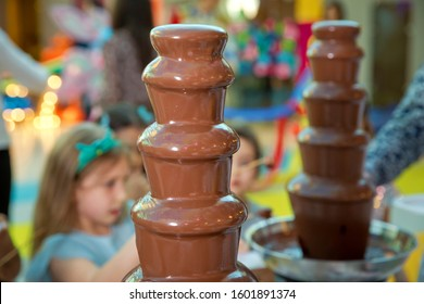 Homemade chocolate fountain fondue with marshmallow on a skewer dripping in chocolate sauce on blurred background and copy space . Chocolate fountain with fruits. Children birthday party
