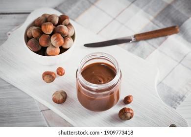 Homemade Chocolate Hazelnut Milk Spread on White wooden Background