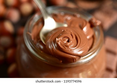 Homemade chocolate hazelnut spread in a vintage jar on a dark brown slate, stone or concrete background.