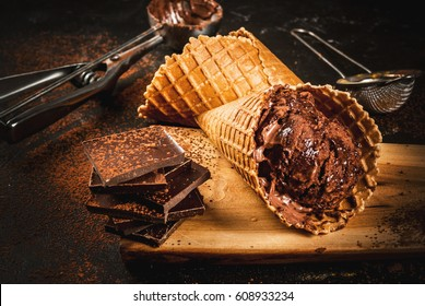 Homemade chocolate ice cream in waffle cones, with a spoon for ice cream, cocoa and pieces of dark chocolate. On a dark gray table, rustic. Copy space