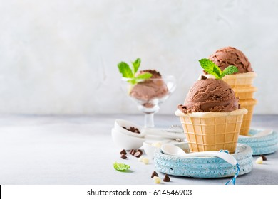 Homemade chocolate ice cream in waffle cups on blue plates on gray stone background. Healthy summer food concept with copy space.