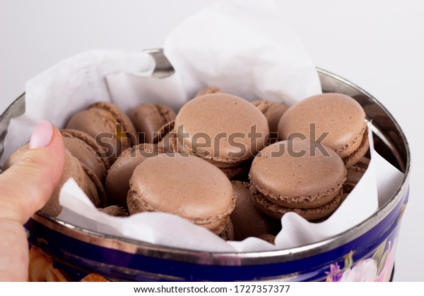 Homemade chocolate macaroons and chocolate cream on a white background