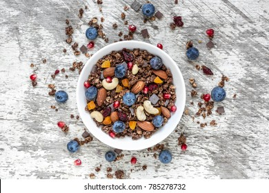 homemade chocolate muesli or granola with berries, dried fruits and nuts. healthy breakfast. top view