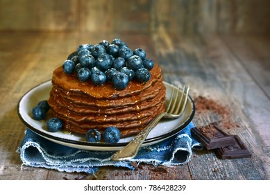 Homemade chocolate pancakes with fresh blueberry and honey on a rustic wooden background.