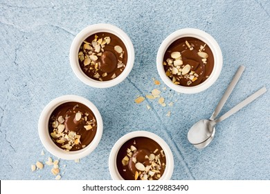 Homemade chocolate pudding in three white ceramic ramekins with roasted almond slivers and teaspoons on light blue concrete background. Top view.